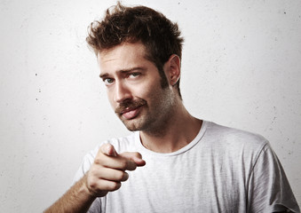 Young mustached man pointing towards the camera