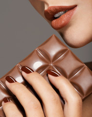 Macro image of female hand with brown nails and bar of chocolate