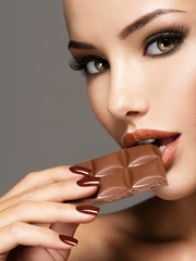 Portrait of  beautiful woman eats sweet chocolate with delight