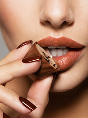 Closeup women mouth with brown candy near lips. Brown manicure.