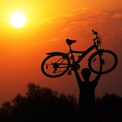Tourist with a bike on the sunset background.
