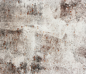Rusty old metallic wall with white paint.