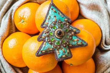 Christmas tree ornament and oranges lying in sack
