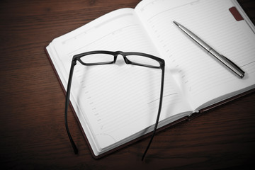 pen, notebook and glasses at brown table