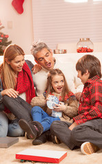 Happy family of four people celebrating Christmas at home. Holid