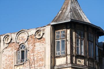 Old unkempt upper part of building on blue sky background