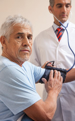 Mature man in 70s measuring blood pressure at hospital. Health c