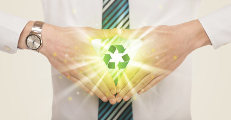 Hands creating a form with recycling sign