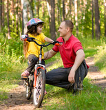 father talking to his daughter, which teaches to ride a bike