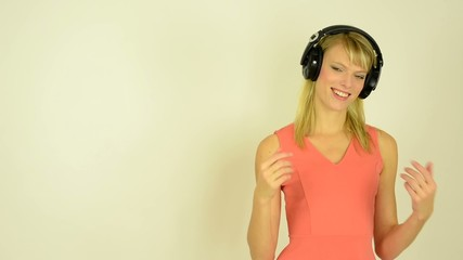 woman listens to music with headphones and woman welcomes