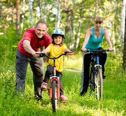 Family having a weekend on their bikes on a summer day in forest