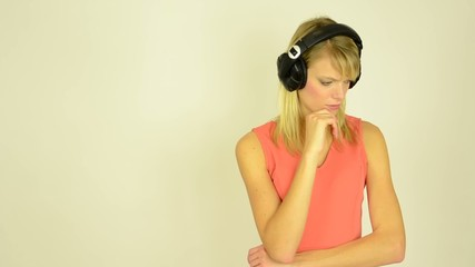 woman listens to music with headphones and woman is thinking