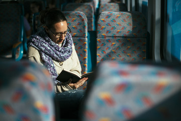 Woman reading book on train
