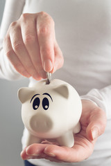 Woman putting coin in piggy coin bank