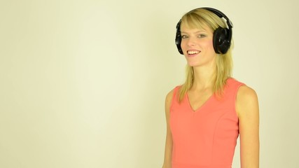 woman listens to music with headphones and dancing - studio