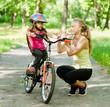 young mother praises her daughter, who learned to ride a bike