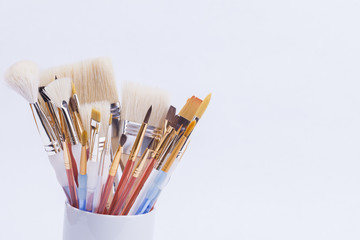 artists paint brushes in cup