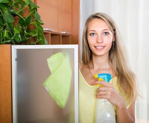 Blonde girl  cleaning glass door of furniture