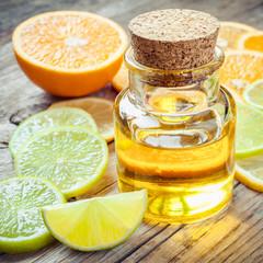 Citrus essential oil and slice of ripe fruits: orange, lemon and