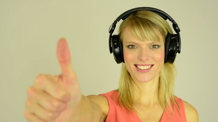 woman listens to music with headphones and shows a thumbs up