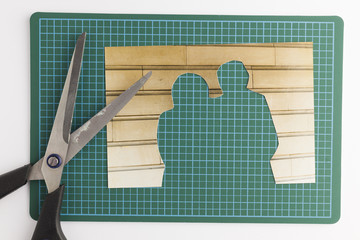 Photograph with cut out people with scissors on green cutting ma