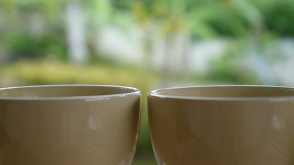 Morning Concept with Two Cups of Hot Coffee Outdoors on Porch.