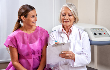 Mature female doctor explaining medical tests to happy woman pat