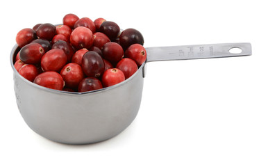 Whole fresh cranberries in a cup measure
