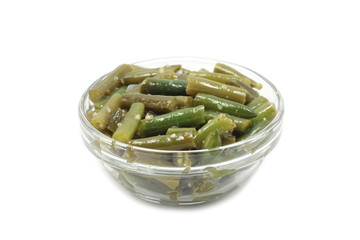 green beans in a glass container on a white background
