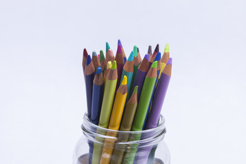 Artists coloured pencils in glass jar