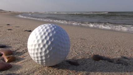 golf  ball on sea resort beach sand - leisure concept