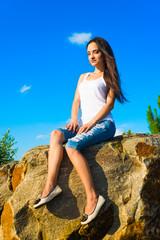 Beautiful girl sitting on a rock