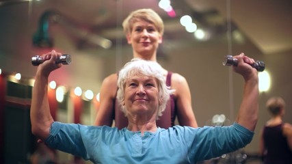 Senior Frau und Trainer mit Hanteln bei Fitness Sport