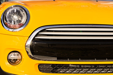 Grille bumper and headlights of yellow sport car