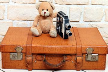 antiker Teddy mit alter Filmkamera auf altem Koffer