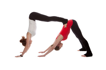 Two girls doing yoga on a white background