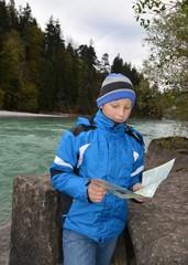 Junge ließt Wanderkarte am Fluss