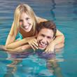 Lachendes Paar badet im Pool im Sommer
