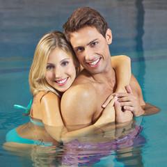 Frau umarmt Mann im Schwimmbad