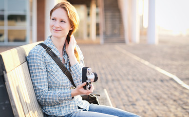 Woman with a Camera in a City at Sunset