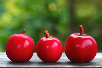 Fresh harvest of ripe red apples on a wooden surface.