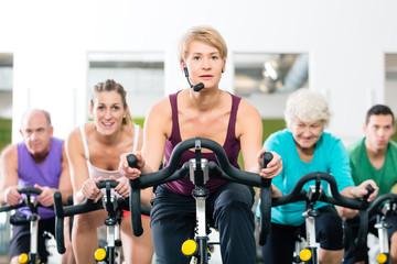 Senioren beim Spinning auf Fitness bike mit Trainer