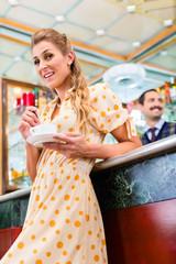 Frau in Kaffeebar trinkt eine Tasse Cappuccino