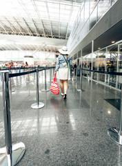 Rear view of woman walking at airport terminal