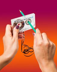 Woman rewind a cassette with a pencil