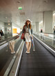 woman wearing hat standing on escalator at airport terminal