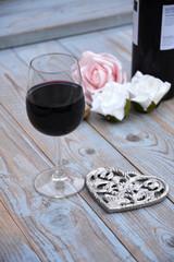glas rode wijn op houten tafel met hart decoratie en roosjes