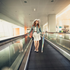 woman in hat with handbag standing on escalator line at airport
