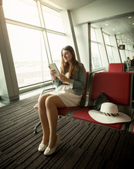woman using digital tablet while waiting for airplane departure