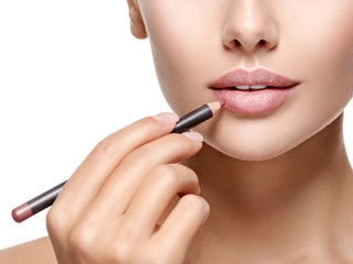 Beautiful woman applying lipstick with cosmetic pencil